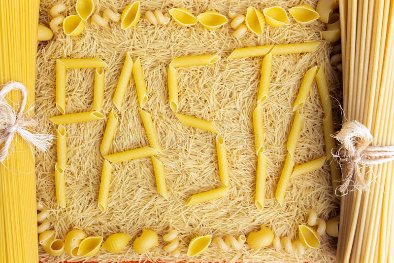 Word pasta made from penne rigate on a background of vermicelli stock photo