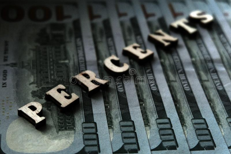 The word PERCENTS is lined with wooden letters on the background of hundred-dollar bills. The concept of financial transactions an stock photography