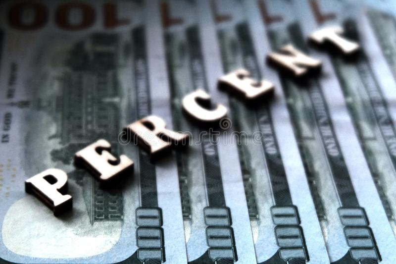 The word PERCENTS is lined with wooden letters on the background of hundred-dollar bills. The concept of financial transactions royalty free stock photography