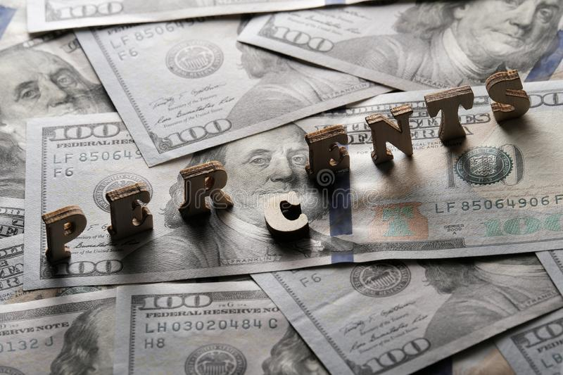 The word PERCENTS is lined with wooden letters on the background of hundred-dollar bills. The concept of financial transactions stock image