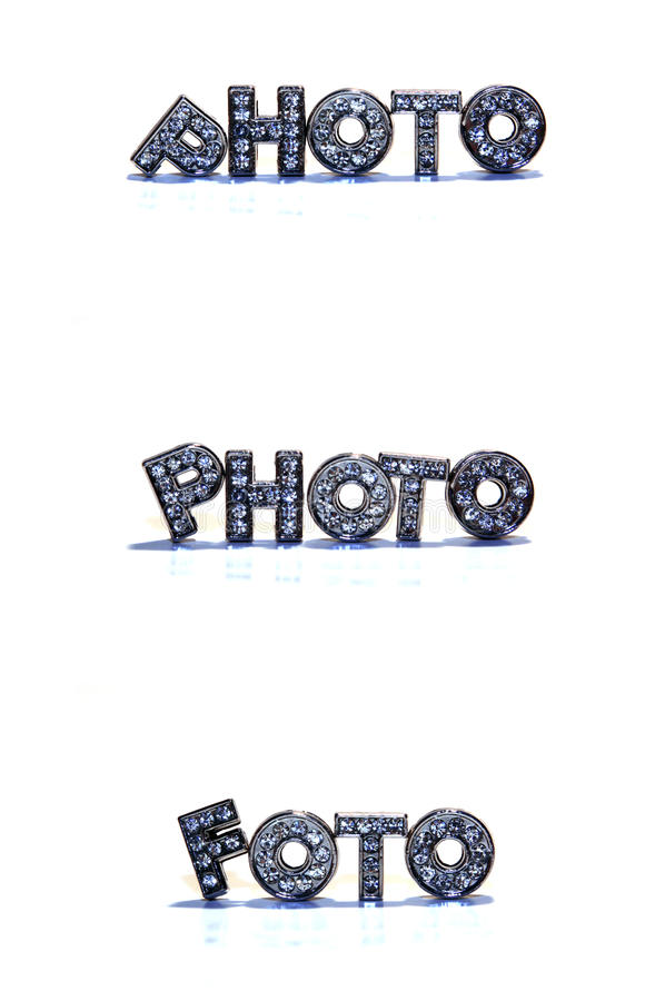 Word PHOTO / FOTO on white background. Letters with rhinestone form the english and german word PHOTO / FOTO isolated on white background, Synonym for Picture stock image
