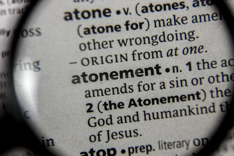 The word or phrase atonement in a dictionary. Book stock photos