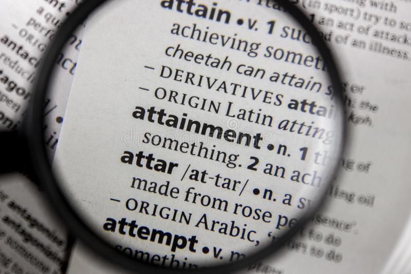 The word or phrase attainment in a dictionary. Book stock photography
