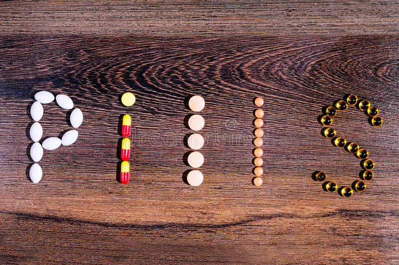 Word `pill` built with tablets. Pharmaceutical medicaments. Word `pill` built with the help of colorful tablets royalty free stock photo