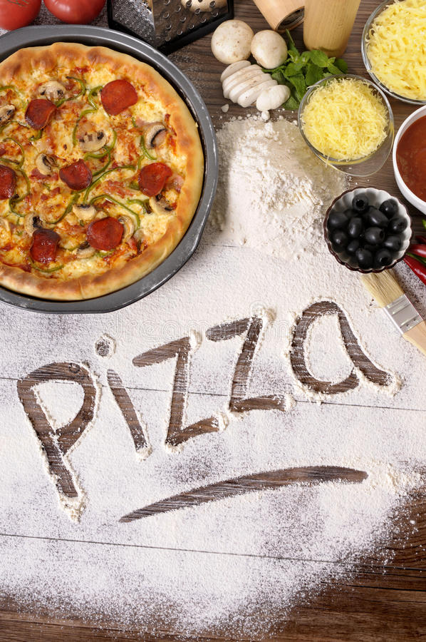 Pizza word written in flour, various ingredients, vertical. The word Pizza written in flour, with freshly baked pepperoni Pizza surrounded by various ingredients stock photo