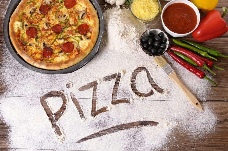 Pizza word written in flour, ingredients, making pizza. The word Pizza written in flour, with freshly baked pepperoni Pizza surrounded by various ingredients royalty free stock images