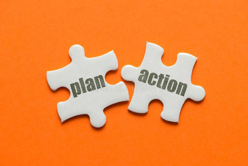 The word Plan Action on two matching puzzle on orange background stock photo