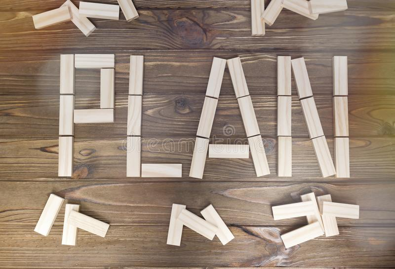 Word plan laid out of wooden blocks on a wooden background. stock photo