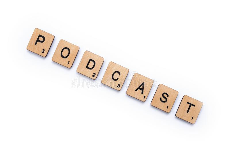 The word PODCAST. London, UK - June 12th 2019: The word PODCAST, spelt with wooden letter tiles over a white background royalty free stock images