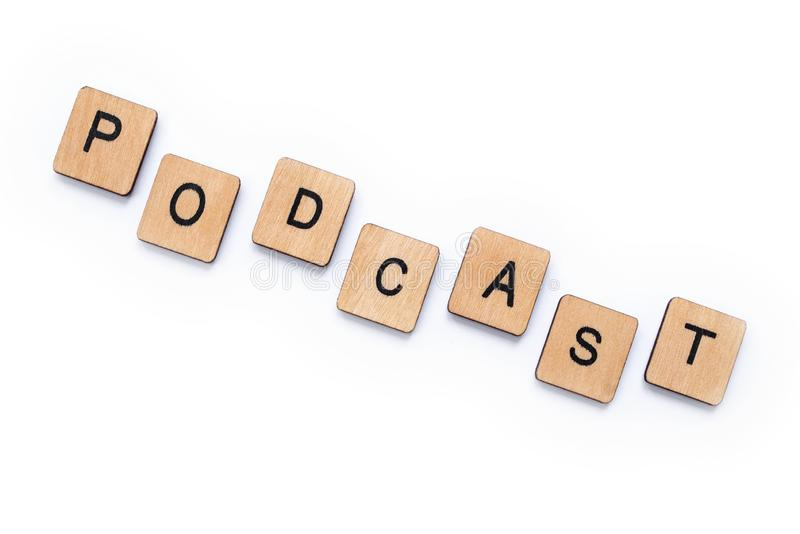 The word PODCAST. Spelt with wooden letter tiles over a white background royalty free stock photography