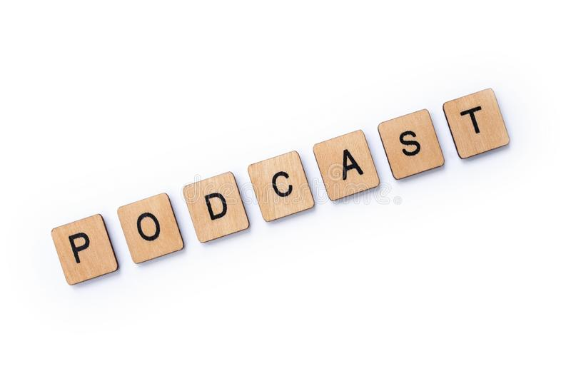 The word PODCAST. Spelt with wooden letter tiles over a white background royalty free stock image