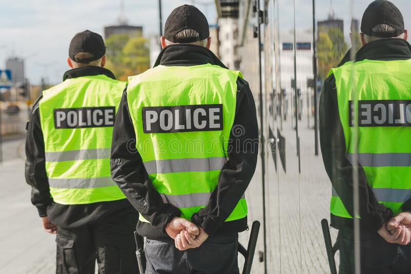 Word police written on reflective vests of police officers royalty free stock photos