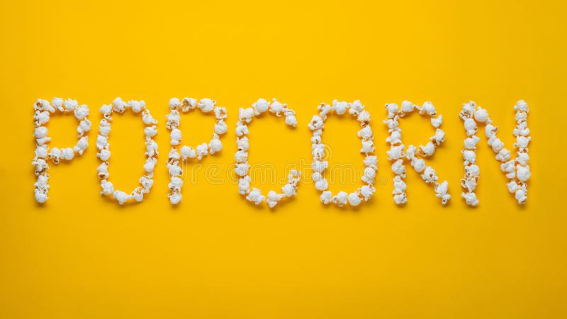 The word POPKORN is laid out from pieces of salt popcorn on a yellow background. Top view. Flat lay stock photography