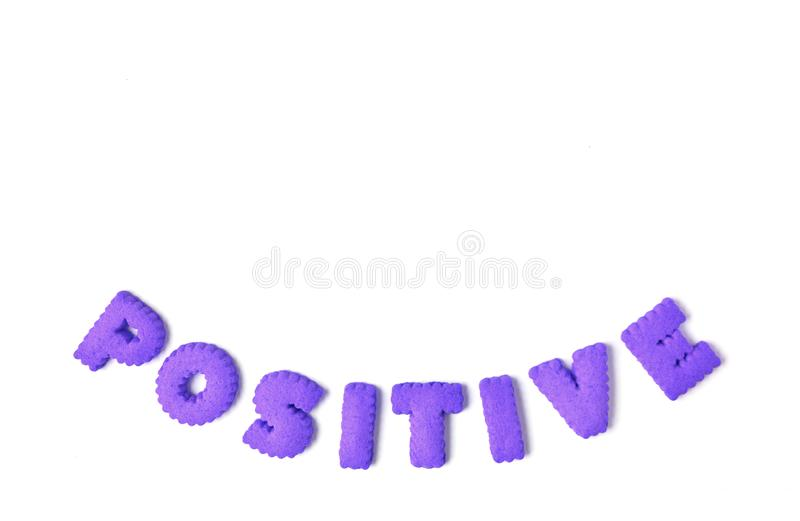 The word POSITIVE spelled with purple color alphabet shaped cookies. On white background royalty free stock photo