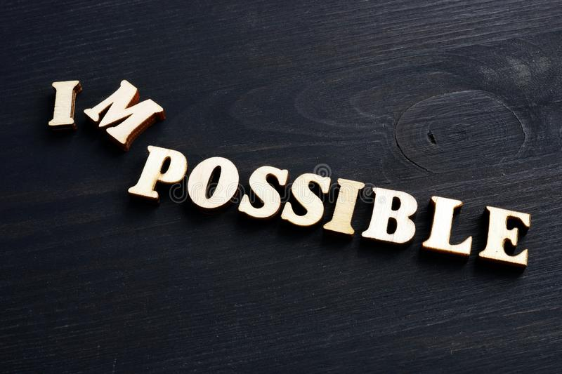 Word possible changed to impossible. Letters on the wood royalty free stock photos
