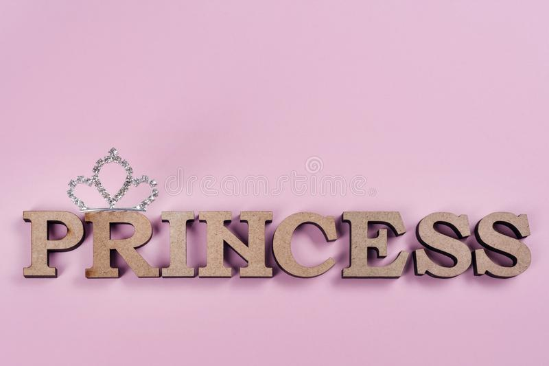 Word Princess abstract wooden letters. Pink background with sparkling crown. royalty free stock photo