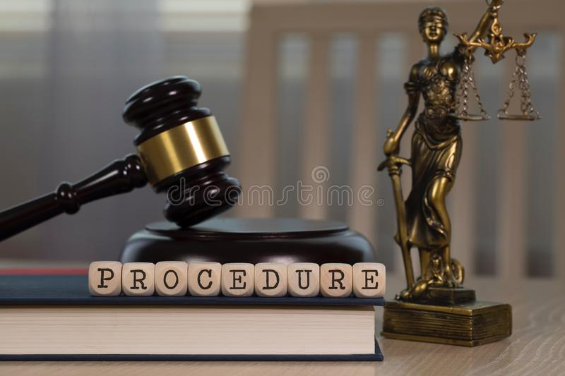 Word PROCEDURE composed of wooden dices. Wooden gavel and statue of Themis in the background stock images