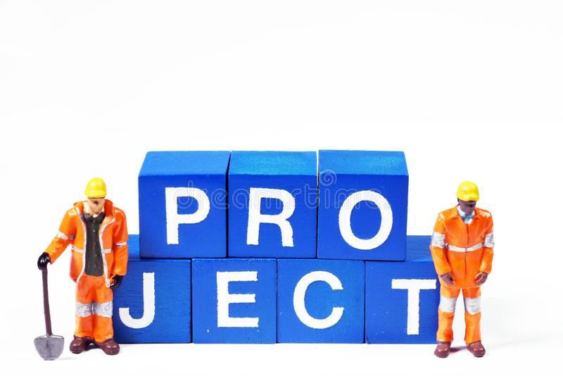 Two blue collar figurines standing next to the word `project` royalty free stock image
