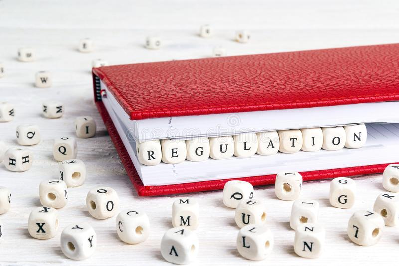 Word Regulation written in wooden blocks in red notebook on whit. E wooden table. Wooden abc stock images