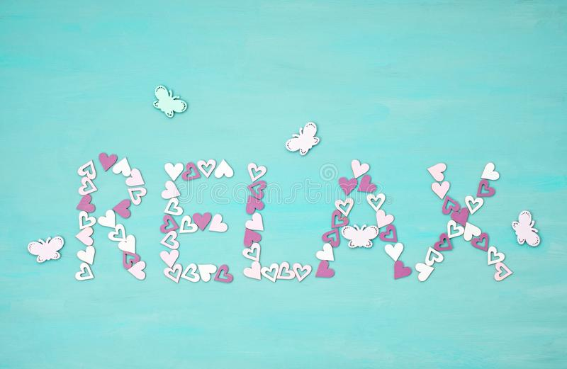 Word RELAX made of small pink hearts over blue background. Wellness, harmony concept royalty free stock photos