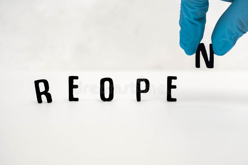 Reopen sign with hand adding the N from above stock image