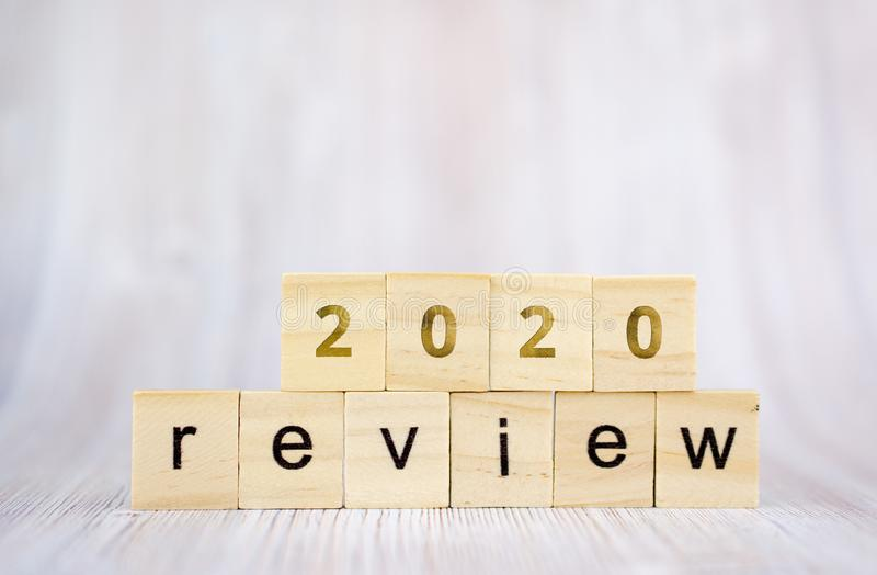 The word review on wooden cube block on white wooden table. 2020 review concept royalty free stock image