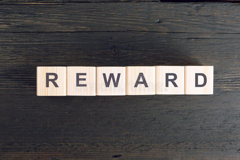 Word REWARD written on a wooden cube. Risk and reward concept royalty free stock photos