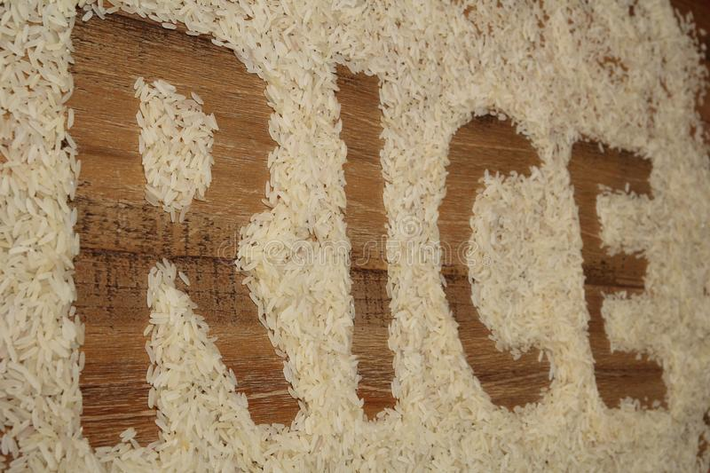 The word RICE written in rice on a wooden background stock photos