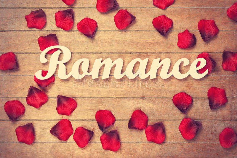 Word Romance And Petals On Wooden Table. Stock Photo ...