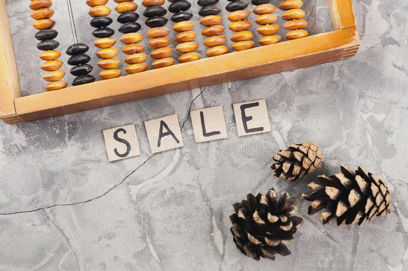 Word SALE laid out of handwritten letters on cardboard squares near old wooden abacus and three cones royalty free stock photography
