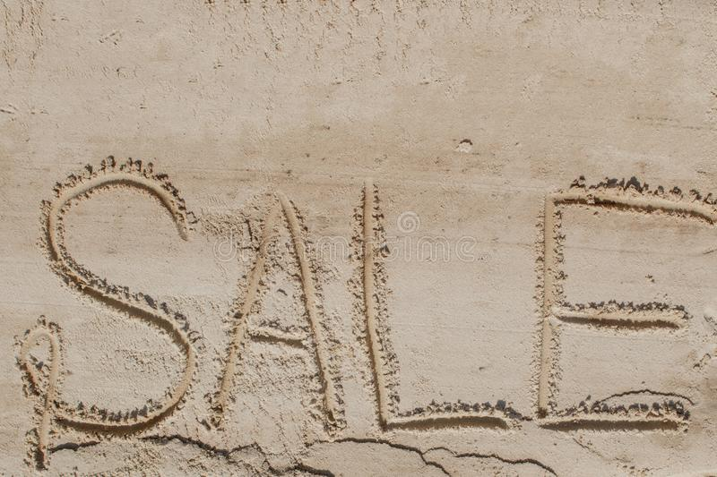 The word sale is painted on the sand. Beach background. View from above. The concept of summer, summer kanikkuly, vacation,. Holydays royalty free stock photos