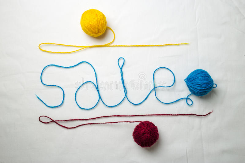 Word sale written multicolored yarn threads coiled into balls. On a white background stock images