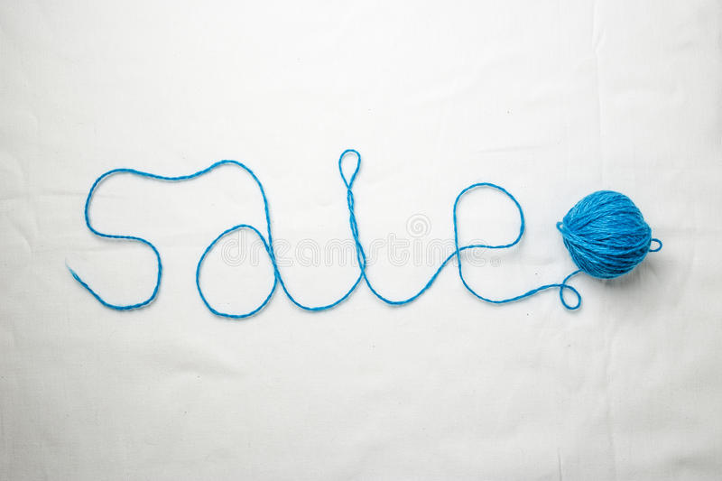 Word sale written by yarn threads coiled into ball. On a white background stock photography