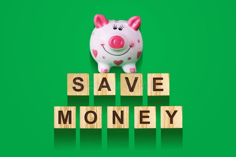 Word Save Money, composed of letters on wooden construction cubes with piggy bank. Green background, isolated Concept business, fi stock images