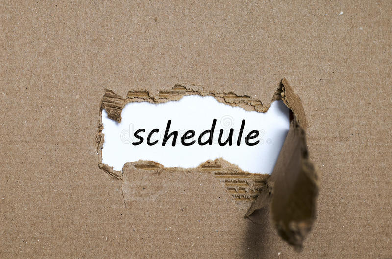 The word schedule appearing behind torn paper stock photos