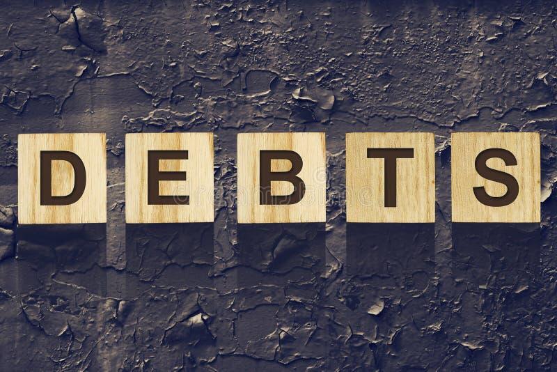 Word schulden, uit brieven op houtconstructiekubussen tegen de achtergrond van oude gekleurd worden samengesteld, barstten ijzer  royalty-vrije stock afbeelding