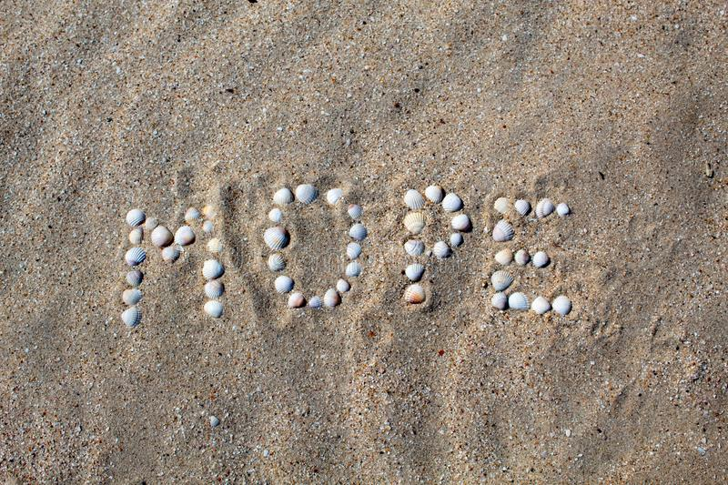 The word sea, in Russian, is laid out on the sand with shells. royalty free stock image