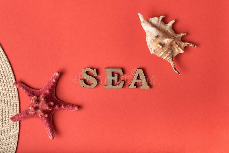 Word Sea from wooden letters. Seashells, starfish and part of a hat. Live coral background. Marine concept.  stock photos
