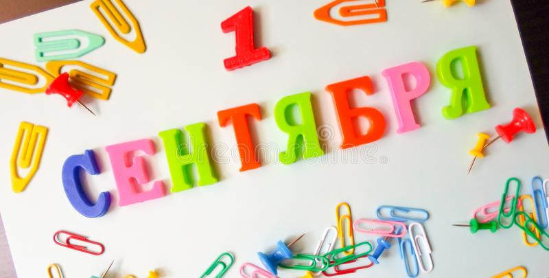 Word September 1 in Russian on a white sheet of paper with paper clips and pins. Back to School concept. Holiday at school stock image