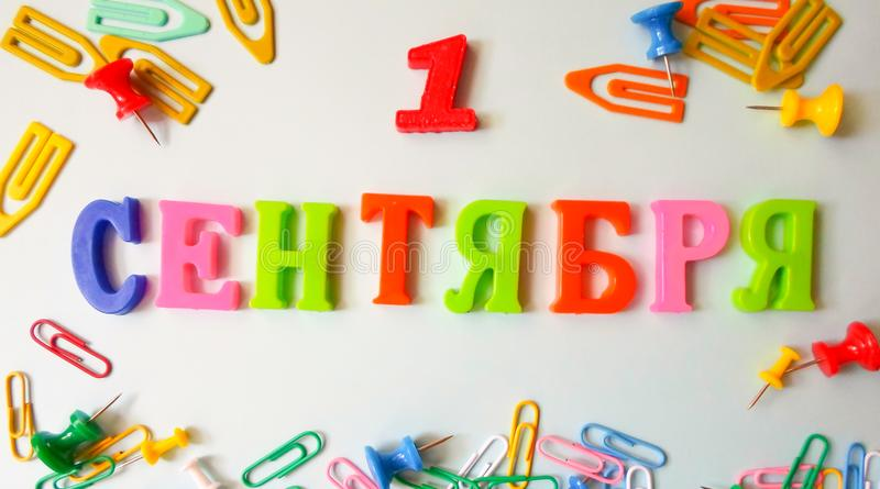 Word September 1 in Russian on a white sheet of paper with paper clips and pins. Back to School concept. Holiday at school stock photography