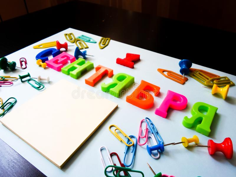 Word September 1 in Russian on a white sheet of paper with paper clips and pins. Back to School concept. Holiday at school royalty free stock images
