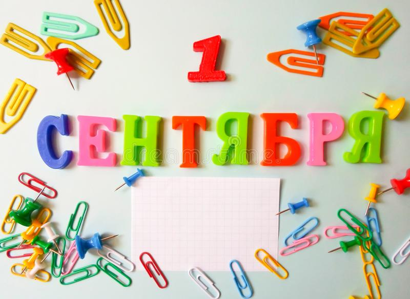 Word September 1 in Russian on a white sheet of paper with paper clips and pins. Back to School concept. Holiday at school royalty free stock photo