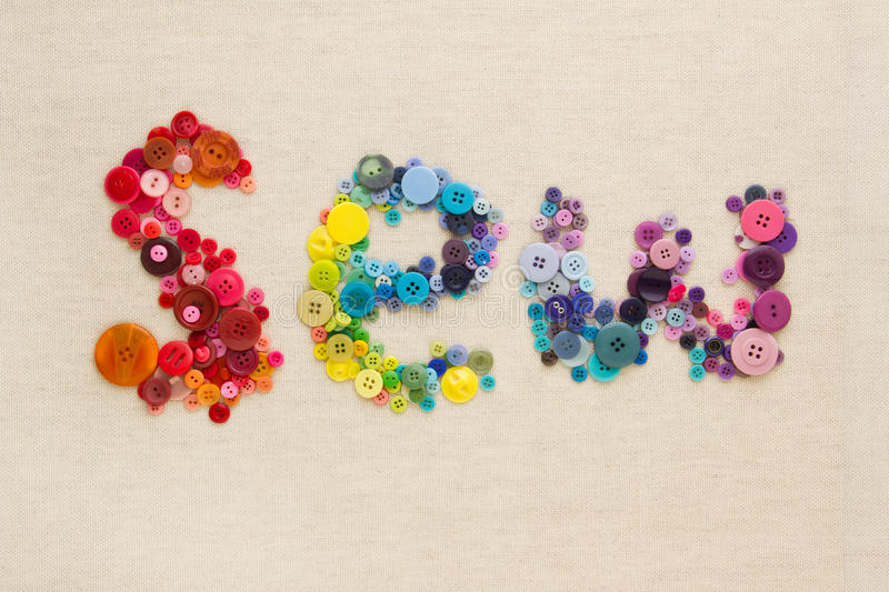 Word. The word SEW spelled out in brightly coloured buttons, arranged in rainbow colour formation - on hessian royalty free stock image
