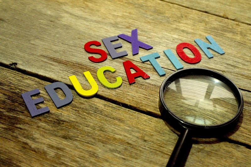 Word SEX EDUCATION colorful wooden alphabet letters set and magnifier on wooden background. Education concept royalty free stock images