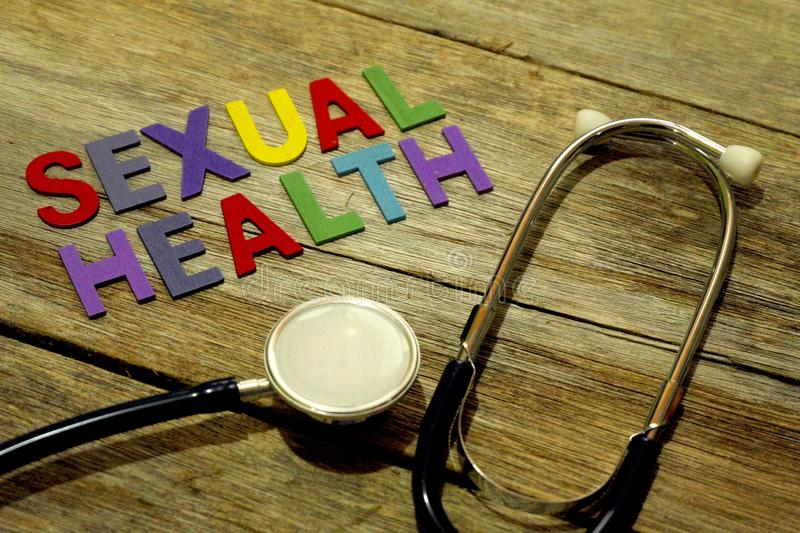 Word SEXUAL HEALTH colorful wooden alphabet letters set and stethoscope on wooden background. Healthcare and medical concept royalty free stock photography