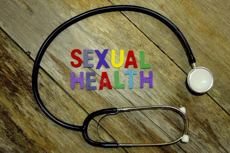 Word SEXUAL HEALTH colorful wooden alphabet letters set and stethoscope on wooden background. Healthcare and medical concept stock image