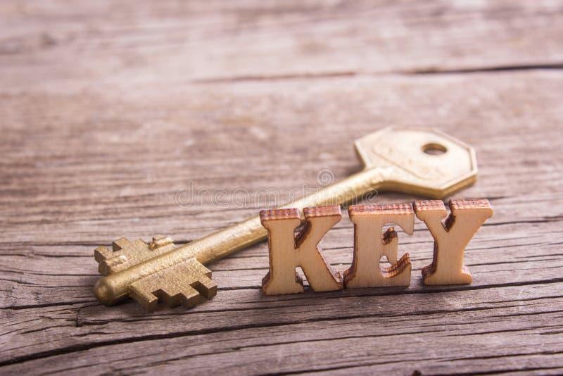 Word sleutel van houten brieven met een sleutel wordt gemaakt die stock fotografie