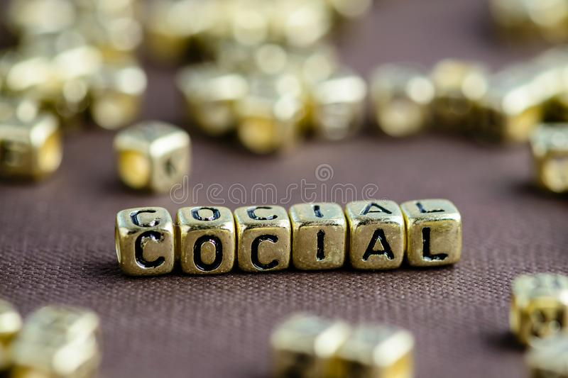 Word SOCIAL made from small golden letters on the brown backgrou stock image