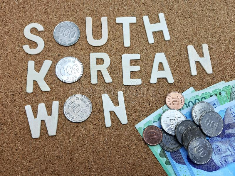 Word of South Korean Won. On cork table with currency coins and bank notes stock photography