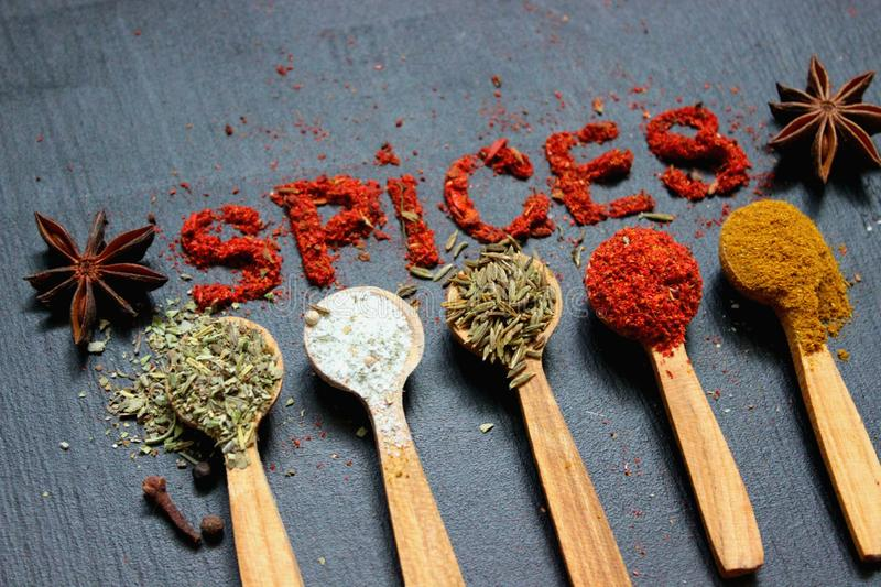 The word spice is written on a black background. Various spices ground turmeric pepper ginger cinnamon herb seasoning salt paprika stock images